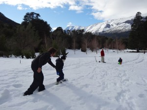 ugando en la nieve en Peuma Hue con snowboards y trineos